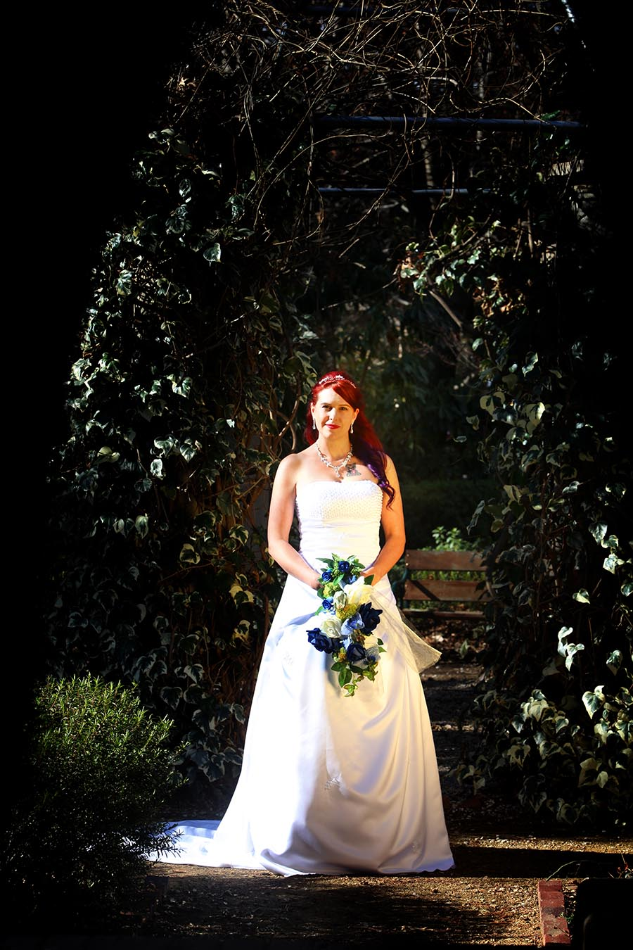 stunning bride with reflected light standing in garden arbour